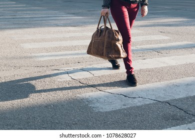 The woman with brown leather bag crosses a pedestrian crossing