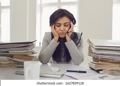 Woman brunette businesswoman in glasses with a mountain of documents on the table tired depressed emaciated disappointed depressive at the table in the office
