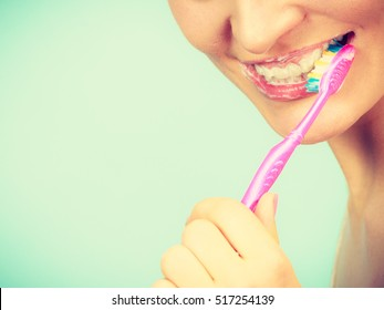 Woman brushing cleaning teeth. Girl with toothbrush. Oral hygiene. Bright green background