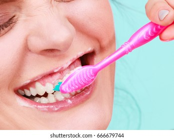 Woman brushing cleaning teeth. Girl with toothbrush close up. Oral hygiene. Blue green background