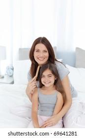 Woman brushing her daughter hair at home