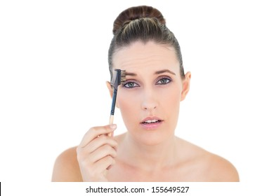 Woman brushing her eyebrow looking shocked at camera against white background