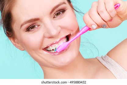 Woman brushing her teeth close up. Oral hygiene. Blue green background