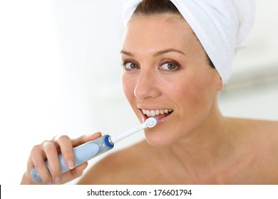 Woman brushing her teeth with electrical toothbrush