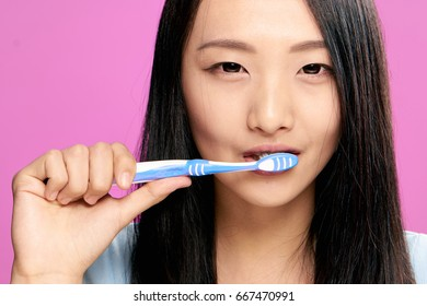 Woman brushing her teeth on a pink background