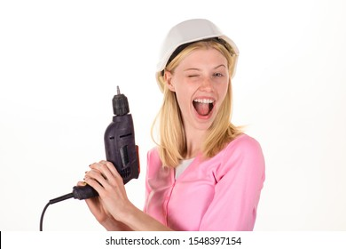 Woman builder with drill. Winking female builder in hard hat hold construction drill. Girl working at flat remodeling. Girl in hardhat with drill. Female construction worker with electric screwdriver
