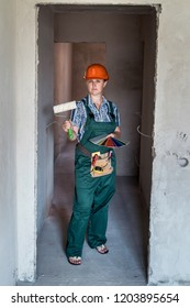 Woman builder in uniform holding painting roll and colour swatch