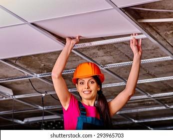 Woman in builder uniform and orange helmet installing suspended ceiling