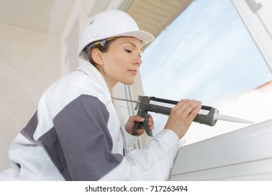woman builder using a silicone gun