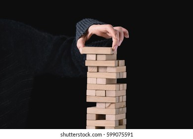 Woman building a tower with wooden puzzles