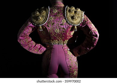 Woman bullfighter with pink costume back on black background