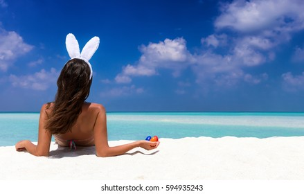 Woman with bunny ears and colorful easter eggs on a tropical beach