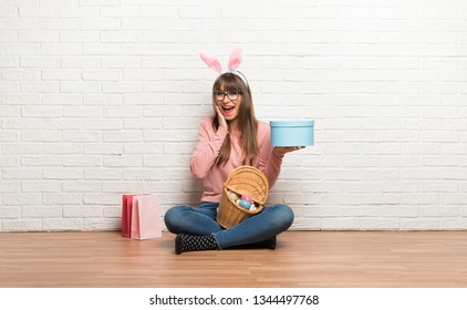 Woman with bunny ears for Easter holidays sitting on the floor surprised because has been given a gift