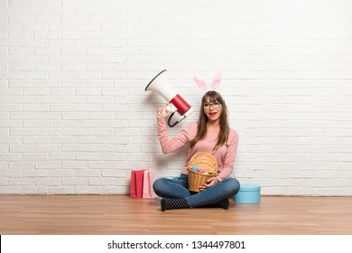 Woman with bunny ears for Easter holidays sitting on the floor holding a megaphone
