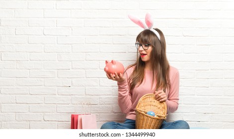 Woman with bunny ears for Easter holidays sitting on the floor surprised while holding a big piggybank