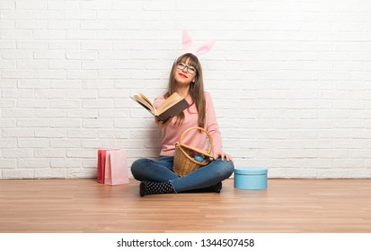Woman with bunny ears for Easter holidays sitting on the floor holding a book and giving it to someone