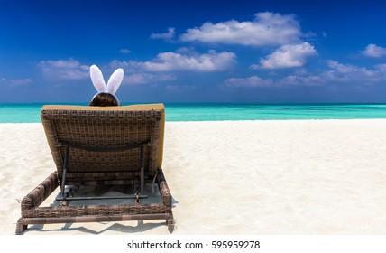 Woman with bunny ears on a sun chair at a tropical beach