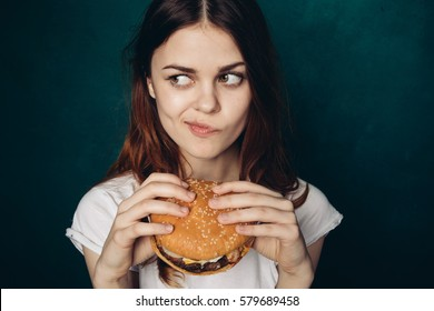 Woman with burger in hand, hungry woman eating a burger and did not want to share a Food