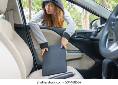 Woman burglar steal a laptop through the window of car - theft concept