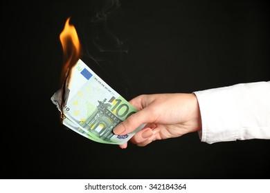Woman burning Euros banknotes on black background