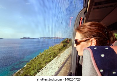 The woman in the bus looks out of the window on a sea landscape
