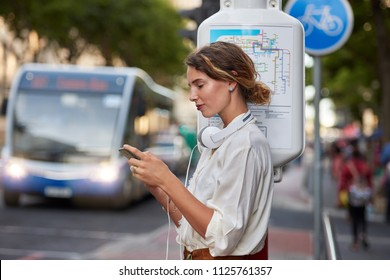 Woman at bus stop with phone app for music headphones in city