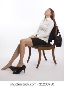Woman in business attire sitting back with shoes off relaxing