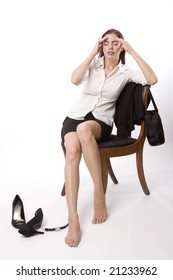 Woman in business attire sitting on a chair and holding her head
