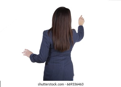 Woman in business attire touching an imaginary touch screen. Brunette is giving a presentation. Isolated on white background back view
