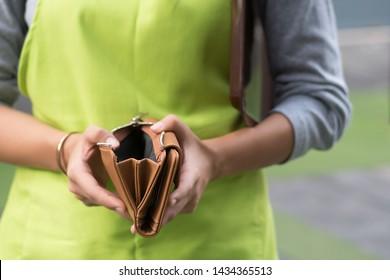 woman business owner having no cash in purse; economic recession, business loss, financial crisis concept