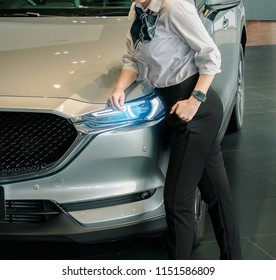 woman business saleman with car in showroom office blurred background.For automotive automobile or transport transportation image.