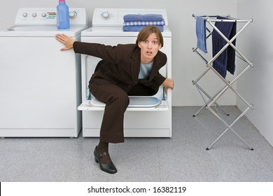 Woman in business suit climbs out of a clothes dryer. Metaphor for the emergence of women and mothers into the business world.