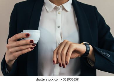 Woman in a business suit holding a cup of coffee and checks the time on a wristwatch