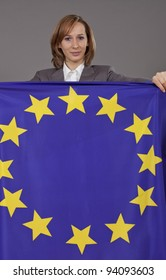 woman in business suit holding european flag over grey background