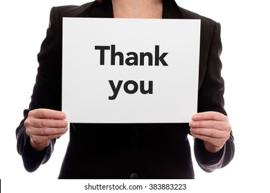 "A woman in a business suit holding a piece of paper saying ""Thank you"""