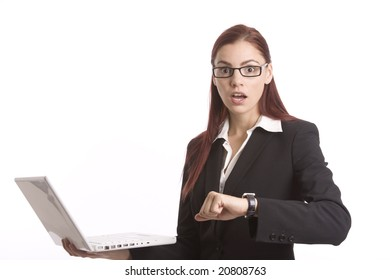 Woman in business suit looking shocked as she looks at her watch and at laptop computer