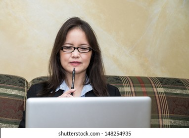 Woman in business suit on sofa in deep thought, with pen and laptop