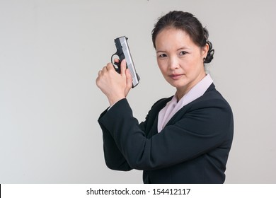 Woman in business suit posing as an agent holding a pistol