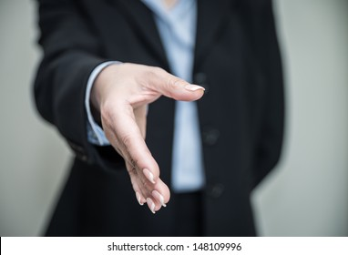 Woman in business suit ready for hand shake with grey background