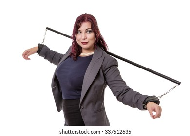Woman in a business suit restrained with handcuffs with a  pole across her shoulders.