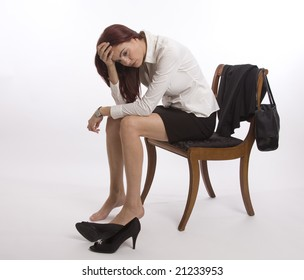 Woman in business suit sitting on a chair looking exhausted