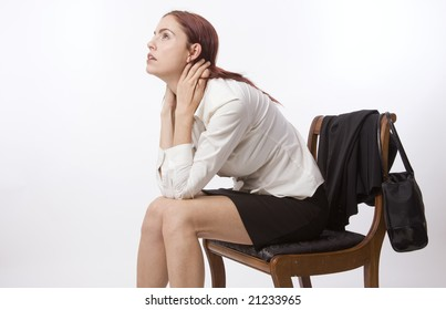 Woman in business suit sitting on chair looking sad and tired