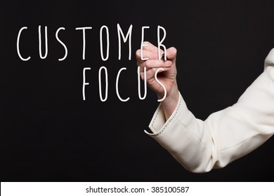 Woman in business suit writing - Customer Focus