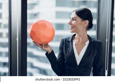 Woman in business suits and black varnished shoes play football in the office. They play an orange soccer ball
