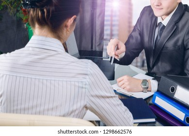 A woman and a businessman are discussing working moments while sitting at a table opposite each other in the office at window view background. The concept is job interview.