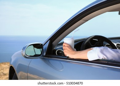 Woman businessman drinking coffee in car interior. Hand holding a cup in window