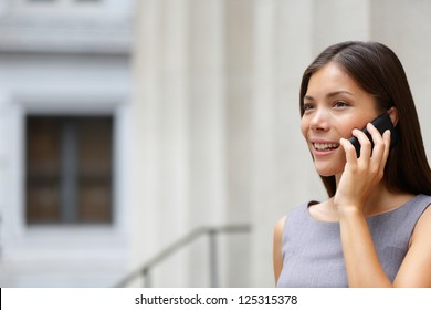 Woman businesswoman lawyer talking on smart-phone outdoors in front of courthouse. Beautiful young mixed race Caucasian / Asian Chinese professional woman.