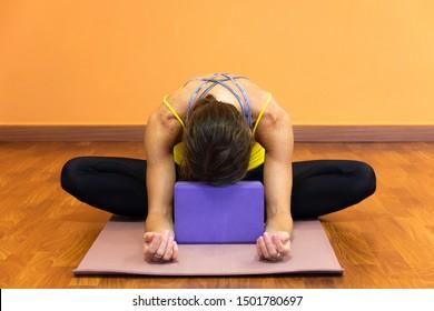 Woman in butterfly yin yoga asana with forehead resting on purple prop. Female yogi on baddha konasana pose on wooden plank floor studio. Relax exercise, flexibility concepts