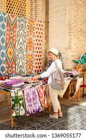 Woman Buy Colorful East Fabric Souvenir. Traditional Uzbekistan Street Handmade Fashion Store. Caucasian Female Buyer at Textile Asian Market