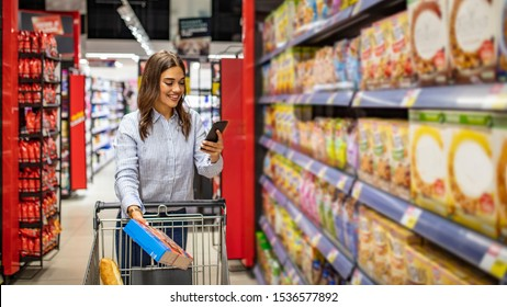 Woman buy products with her trolley at supermarket. Pretty woman buying groceries in a supermarket/mall/grocery store. Shopping list. Smiling beautiful woman stands with phone near products in store